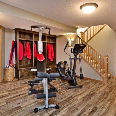 Basement - mid-sized traditional look-out medium tone wood floor basement idea in Minneapolis with beige walls, no fireplace and a stone fireplace