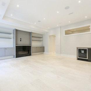Idées déco pour un grand sous-sol classique donnant sur l'extérieur avec un mur blanc, un sol en marbre, une cheminée standard, un manteau de cheminée en pierre et un sol beige.