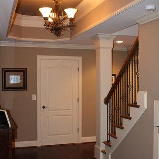 Cette image montre un grand sous-sol traditionnel donnant sur l'extérieur avec un mur beige, un sol en bois foncé et un poêle à bois.