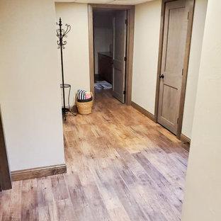 Idée de décoration pour un grand sous-sol chalet semi-enterré avec un bar de salon, un mur beige, un sol en vinyl et un sol marron.