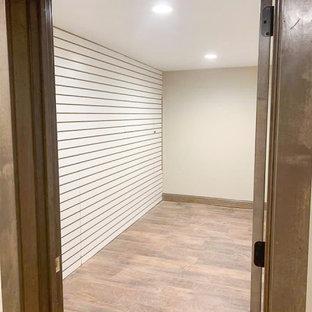 Cette image montre un grand sous-sol chalet semi-enterré avec un bar de salon, un mur beige, un sol en vinyl et un sol marron.