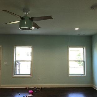 Cette image montre un grand sous-sol traditionnel donnant sur l'extérieur avec un sol en bois foncé et un mur vert.