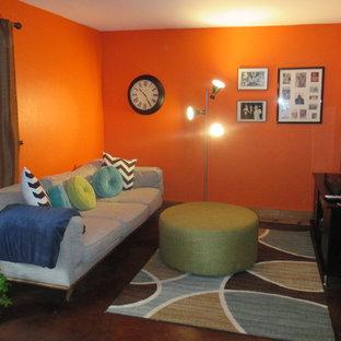 Exemple d'un petit sous-sol rétro donnant sur l'extérieur avec un mur orange, béton au sol, un poêle à bois, un manteau de cheminée en pierre et un sol marron.