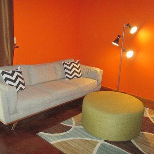 Ejemplo de sótano con puerta vintage, pequeño, con parades naranjas, suelo de cemento, estufa de leña, marco de chimenea de piedra y suelo marrón