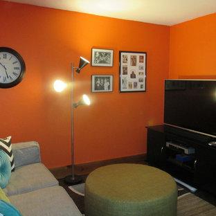 Aménagement d'un petit sous-sol rétro donnant sur l'extérieur avec un mur orange, béton au sol, un poêle à bois, un manteau de cheminée en pierre et un sol marron.
