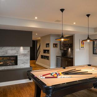 Inspiration pour un sous-sol design enterré et de taille moyenne avec un mur beige, sol en stratifié, une cheminée double-face, un manteau de cheminée en carrelage et un sol marron.
