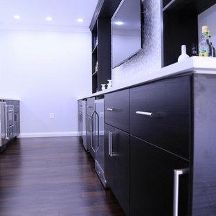 Inspiration pour un grand sous-sol design donnant sur l'extérieur avec un mur gris, sol en stratifié, une cheminée standard, un manteau de cheminée en carrelage et un sol marron.