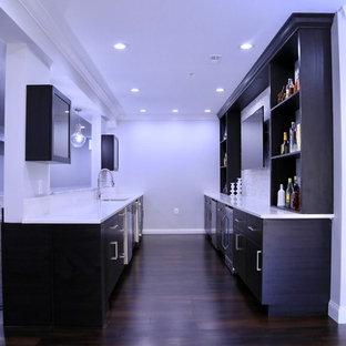 Cette image montre un grand sous-sol design donnant sur l'extérieur avec un mur gris, sol en stratifié, une cheminée standard, un manteau de cheminée en carrelage et un sol marron.