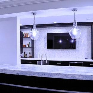 Idée de décoration pour un grand sous-sol design donnant sur l'extérieur avec un mur gris, sol en stratifié, une cheminée standard, un manteau de cheminée en carrelage et un sol marron.