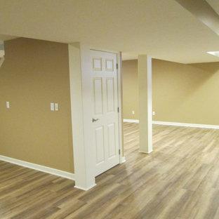 Immagine di una taverna interrata con pareti beige, pavimento in vinile e pavimento beige