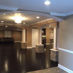 Cette photo montre un sous-sol chic donnant sur l'extérieur et de taille moyenne avec un mur beige, un sol en bambou, cheminée suspendue, un manteau de cheminée en pierre et un sol marron.