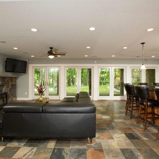 Exemple d'un grand sous-sol chic donnant sur l'extérieur avec un mur gris, un sol en ardoise et un poêle à bois.