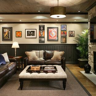 Inredning av en klassisk stor källare utan fönster, med beige väggar, mellanmörkt trägolv, en standard öppen spis och gult golv