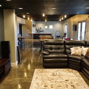 Idée de décoration pour un grand sous-sol minimaliste donnant sur l'extérieur avec un mur gris, béton au sol, aucune cheminée et un sol gris.