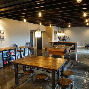 Cette image montre un grand sous-sol minimaliste donnant sur l'extérieur avec un mur gris, béton au sol, aucune cheminée et un sol gris.
