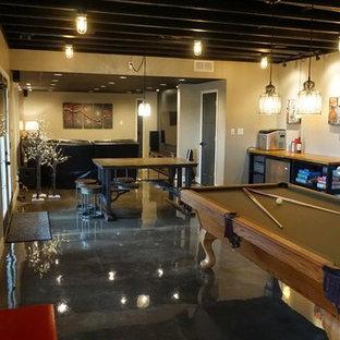 Cette photo montre un grand sous-sol moderne donnant sur l'extérieur avec un mur gris, béton au sol, aucune cheminée et un sol gris.