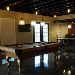 Réalisation d'un grand sous-sol minimaliste donnant sur l'extérieur avec un mur gris, béton au sol et un sol noir.