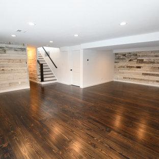 Diseño de sótano con puerta retro, grande, sin chimenea, con paredes blancas, suelo de madera en tonos medios y suelo marrón