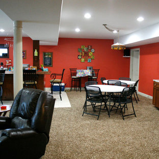 Huge trendy walk-out carpeted basement photo in Detroit with orange walls