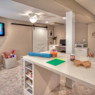 Réalisation d'un très grand sous-sol design donnant sur l'extérieur avec un mur beige, un sol en vinyl et une cheminée standard.