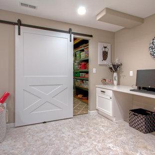 Réalisation d'un très grand sous-sol design donnant sur l'extérieur avec un mur beige et un sol en vinyl.