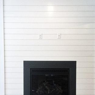 Aménagement d'un sous-sol contemporain semi-enterré et de taille moyenne avec un mur blanc, un sol en vinyl, une cheminée standard et un sol marron.