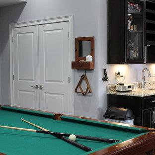 Exemple d'un grand sous-sol craftsman donnant sur l'extérieur avec un mur gris, béton au sol et un sol multicolore.