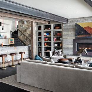 Idées déco pour un sous-sol montagne avec un mur beige, un manteau de cheminée en bois, une cheminée ribbon et un sol noir.