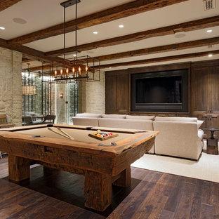 Cette image montre un très grand sous-sol traditionnel donnant sur l'extérieur avec un mur beige, un sol en bois foncé, un sol marron et salle de jeu.
