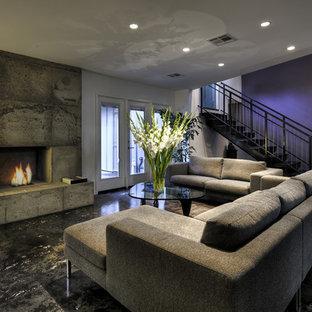 Aménagement d'un sous-sol contemporain donnant sur l'extérieur avec un mur violet, une cheminée standard, béton au sol et un manteau de cheminée en béton.