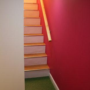 Cette image montre un sous-sol bohème de taille moyenne avec un mur rose, un sol en vinyl, une cheminée standard, un manteau de cheminée en pierre et un sol vert.