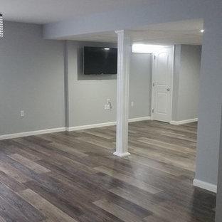Idée de décoration pour un grand sous-sol tradition enterré avec un mur gris, un sol en bois brun, aucune cheminée et un sol marron.