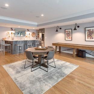 Idées déco pour un grand sous-sol craftsman donnant sur l'extérieur avec un bar de salon, un mur gris, un sol en bois brun et un plafond à caissons.