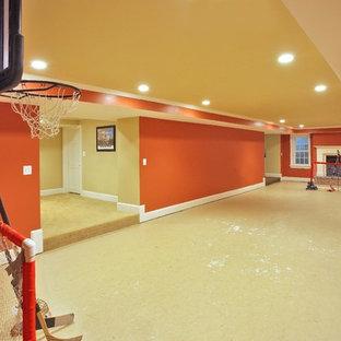 Cette image montre un grand sous-sol traditionnel avec un mur orange et béton au sol.
