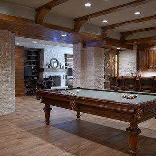 Idée de décoration pour un grand sous-sol tradition semi-enterré avec un mur beige, un sol en bois brun, une cheminée standard, un sol marron et salle de jeu.
