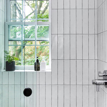 Glass-enclosed shower with vertically-stacked subway tile