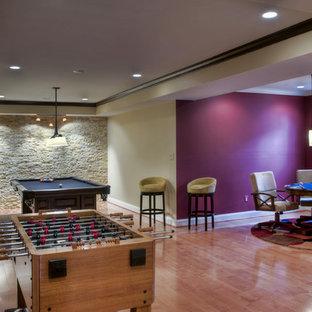 Cette photo montre un sous-sol tendance donnant sur l'extérieur et de taille moyenne avec un mur rose et un sol en bois brun.