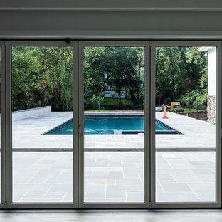 Aménagement d'un sous-sol contemporain donnant sur l'extérieur et de taille moyenne avec un mur blanc, un sol en carrelage de céramique, aucune cheminée et un sol marron.