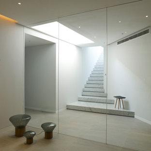 Aménagement d'un grand sous-sol contemporain semi-enterré avec salle de jeu, un mur blanc, un sol en carrelage de porcelaine, un sol beige et un plafond décaissé.