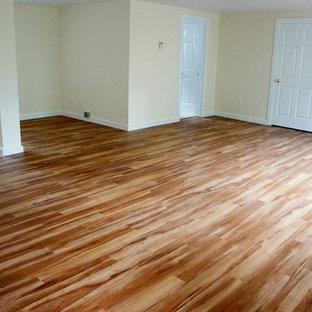 Cette image montre un sous-sol traditionnel semi-enterré et de taille moyenne avec un mur beige et un sol en bois brun.