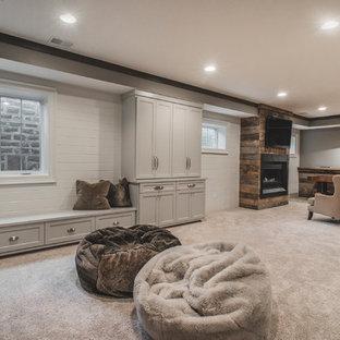 Cette image montre un grand sous-sol chalet semi-enterré avec un mur gris, moquette, une cheminée ribbon et un manteau de cheminée en métal.