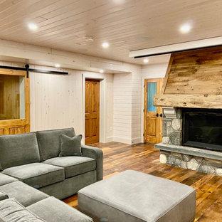 Inspiration pour un sous-sol craftsman donnant sur l'extérieur et de taille moyenne avec salle de jeu, un mur blanc, un sol en bois brun, une cheminée standard, un manteau de cheminée en pierre, un sol marron, un plafond en lambris de bois et du lambris de bois.
