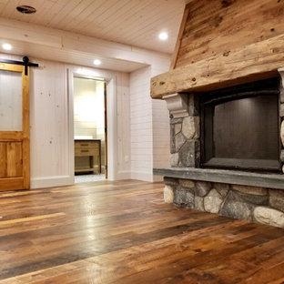 Idée de décoration pour un sous-sol craftsman donnant sur l'extérieur et de taille moyenne avec salle de jeu, un mur blanc, un sol en bois brun, une cheminée standard, un manteau de cheminée en pierre, un sol marron, un plafond en lambris de bois et du lambris de bois.