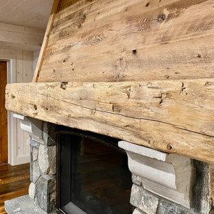 Cette image montre un sous-sol craftsman donnant sur l'extérieur et de taille moyenne avec salle de jeu, un mur blanc, un sol en bois brun, une cheminée standard, un manteau de cheminée en pierre, un sol marron, un plafond en lambris de bois et du lambris de bois.