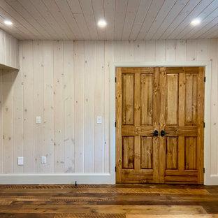 Exemple d'un sous-sol craftsman donnant sur l'extérieur et de taille moyenne avec salle de jeu, un mur blanc, un sol en bois brun, une cheminée standard, un manteau de cheminée en pierre, un sol marron, un plafond en lambris de bois et du lambris de bois.