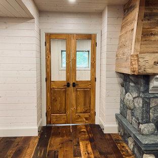 Réalisation d'un sous-sol craftsman donnant sur l'extérieur et de taille moyenne avec salle de jeu, un mur blanc, un sol en bois brun, une cheminée standard, un manteau de cheminée en pierre, un sol marron, un plafond en lambris de bois et du lambris de bois.