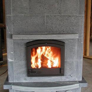 Cette image montre un sous-sol design avec un poêle à bois et un manteau de cheminée en pierre.