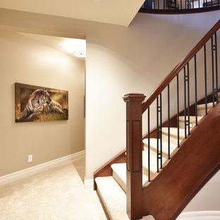 Idée de décoration pour un grand sous-sol tradition donnant sur l'extérieur avec un mur beige, moquette, une cheminée standard, un manteau de cheminée en bois et un sol beige.