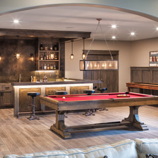 Cette image montre un très grand sous-sol chalet semi-enterré avec un mur gris, un sol en bois brun, un sol marron, boiseries et salle de jeu.