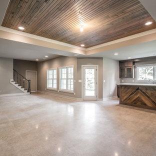 Réalisation d'un sous-sol donnant sur l'extérieur avec un bar de salon, un mur gris, béton au sol, un sol gris et un plafond en bois.